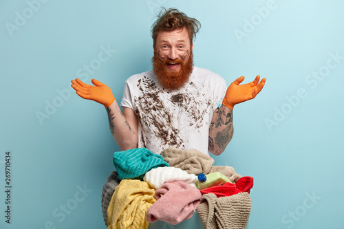 Cuadros en Lienzo Happy red haired man with thick bristle, spreads hands, has fun after doing laundry at home, dressed in white dirty t shirt, poses over blue background