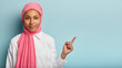 Leinwanddruck Bild - Photo of healthy Muslim woman points aside with index finger on free space, has no make up, wrapped in pink veil, dressed in white shirt, isolated over blue background. Arabic female poses indoor