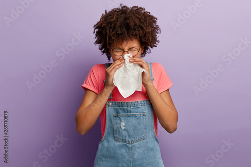 Photo  Curly young female feels unwell, blows nose in white tissue, suffers from runnin
