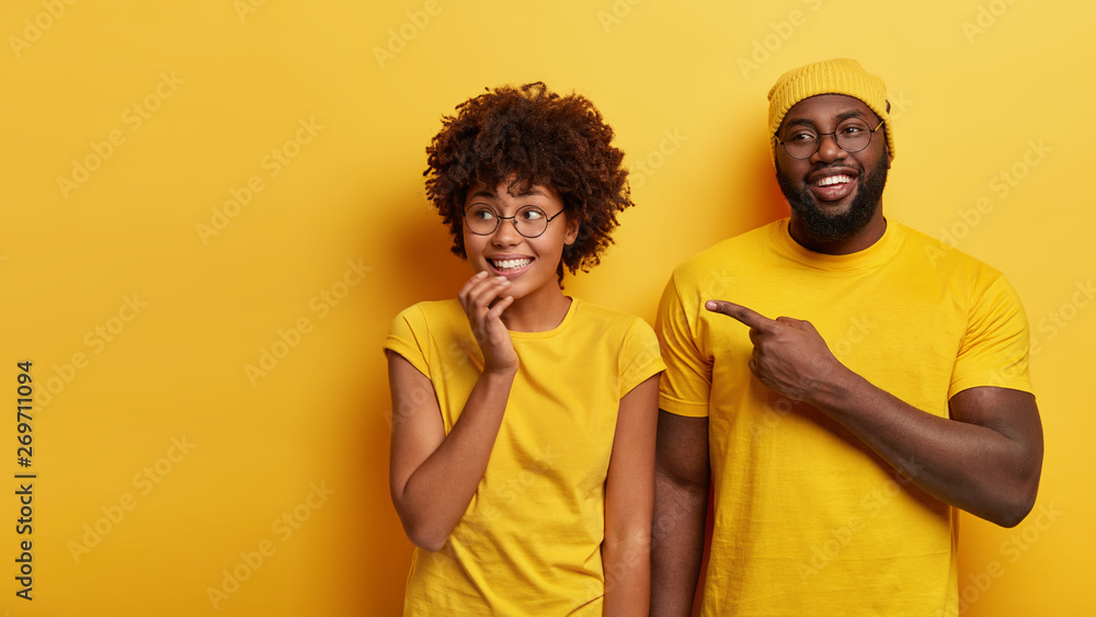 Fototapeta Studio shot of happy young woman and man look happily aside, point at blank space, notices awesome product, stand against yellow studio background. People, advertisement and ethnicity concept