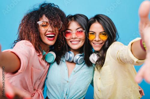Joyful hispanic girl in yellow cotton shirt making selfie with her international female friends Canvas Print