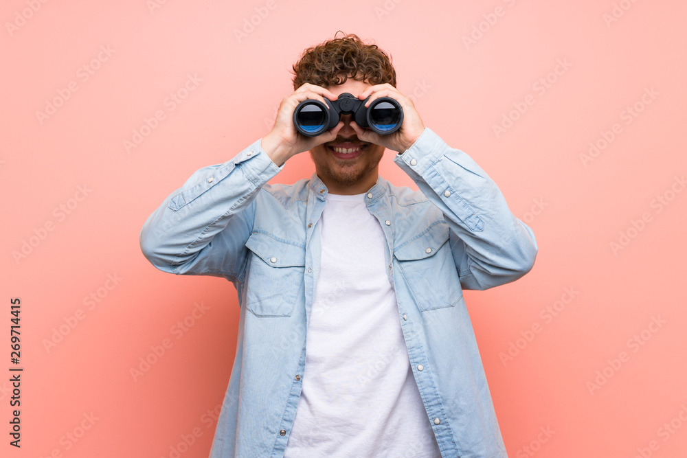 Fototapeta Blonde man over pink wall and looking in the distance with binoculars