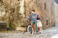 Young Attractive Tourist Couple In Casual Clothing, Bearded Man And Blond Woman Sightseeing On Modern Tandem Bicycle On Lit By Bright Sun Empty Pavement At The Corner Of Ancient High Stone Building.