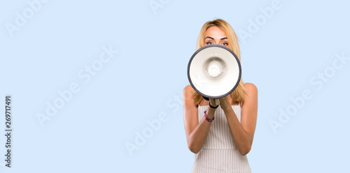 Photo  Young blonde woman shouting through a megaphone over isolated blue background