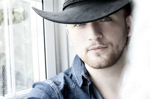 Fototapeta Portrait  of handsome cowboy with blue shirt and eyes