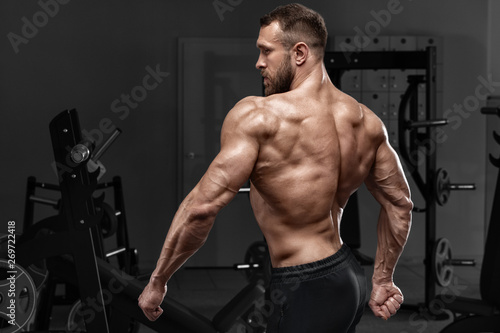 fototapeta na drzwi i meble Rear view muscular man showing back muscles at the gym. Strong male naked torso, workout