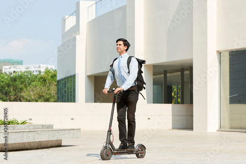 Fotografia  Young smiling manager with backpack behind his back riding on electric scooter p