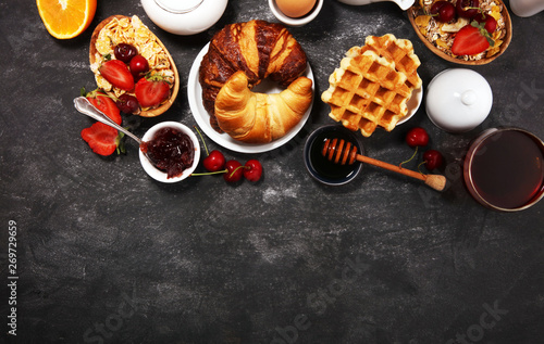Huge healthy breakfast on table with coffee, orange juice, fruits, waffles and croissants Wallpaper Mural