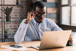 Handsome african businessman holding his eyeglasses, working with laptop in modern loft office