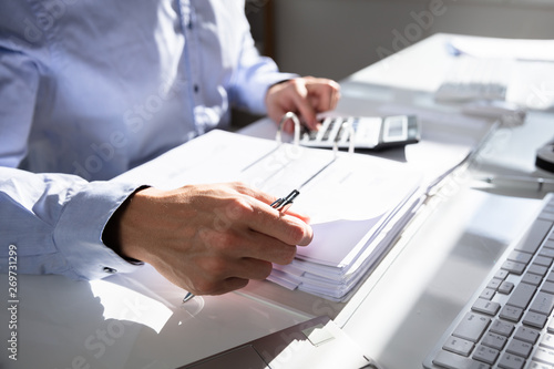 Businessperson Calculating Invoice - 269731299