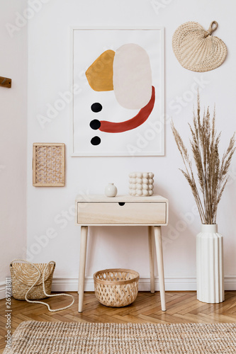 Photo  Stylish white interior of living room with mock up poster frame, rattan accessories, leaf, wooden shelf, vase with flowers and elegant personal stuff