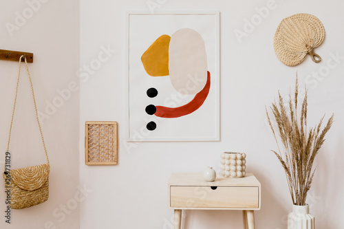 Stylish white interior of living room with mock up poster frame, rattan accessories, leaf, wooden shelf, vase with flowers and elegant personal stuff Wallpaper Mural