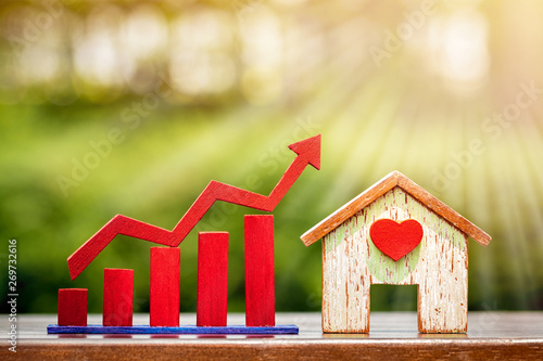 Fotografía  Home with red heart and bar graph with growing value put on table on bokeh background in the public park, for financial business investment and fund real estate concept