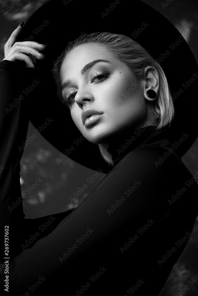 Fototapeta black and white portrait of beautiful fashionable blonde girl in hat