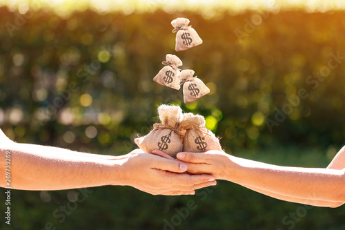 Fotografía  Women and man hands hold a money bags and dropping on the top in the public park for loans to planned investment is together in the future concept