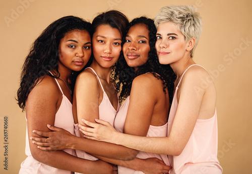 Fotografie, Obraz  Four beautiful women hugging each other in a studio