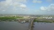 Wide angle shot of high flying drone passing over Jules Wijdenbosch Bridge between Paramaribo and Meerzorg in Suriname with panoramic view of river, port, landscape and town in background.