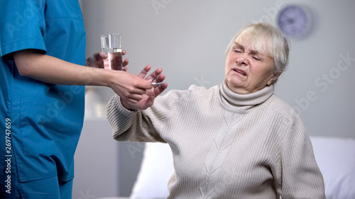 Photo  Capricious old woman rejecting medication from medical worker, treatment