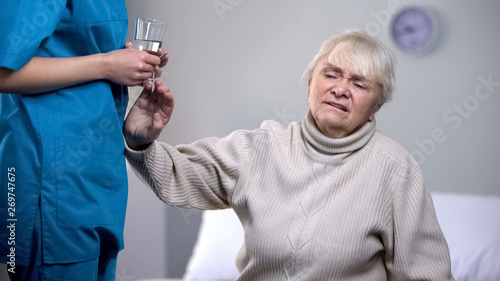 Fotografía  Old woman rejecting medication from nurse in rehabilitation center, treatment