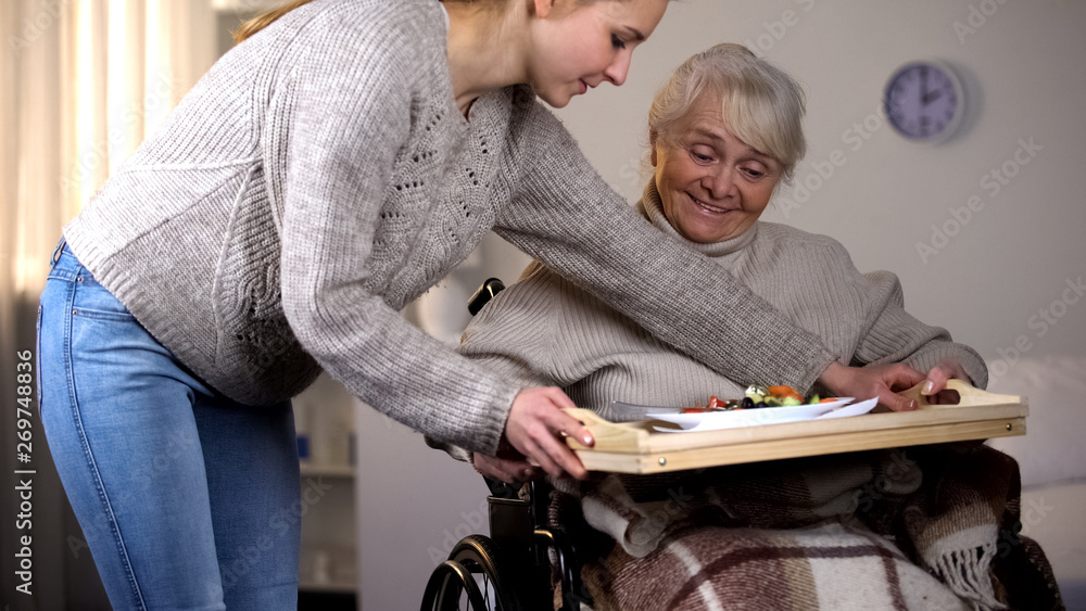 Fototapeta Female volunteer serving dinner to handicapped old woman, elder care, help