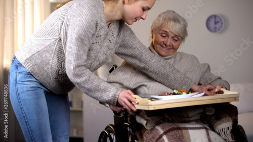 Fotomural  Female volunteer serving dinner to handicapped old woman, elder care, help