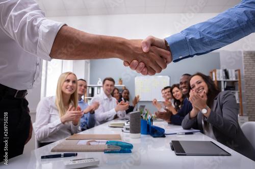 Team Leader Handshaking In Front Of Employee Congratulating