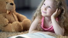 Smiling Kid Shining With Happiness And Looking Dreamy, Lying On Floor With Book