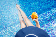 Woman In A Blue Hat Relaxing At The Pool With A  Cocktail