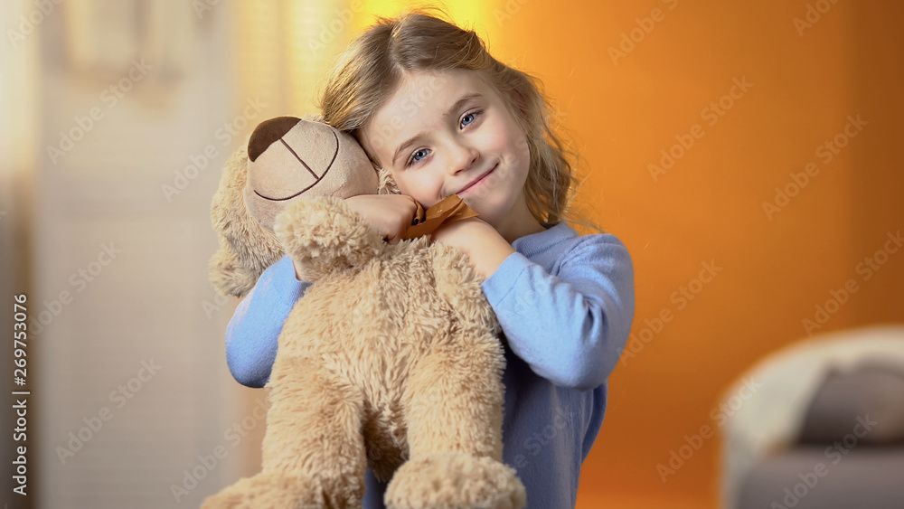 Beautiful girl with favourite teddy bear toy smiling at camera, happy childhood