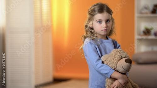 Fotografija Adorable sad little girl hugging favorite teddy bear feeling lonely in orphanage
