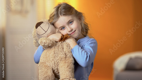 Fototapeta Cute curly-haired blond girl hugging teddy bear and smiling at camera, happiness obraz na płótnie