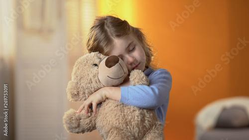 Fototapeta Little lonely girl hugging teddy bear, suffering loneliness, family problems obraz na płótnie