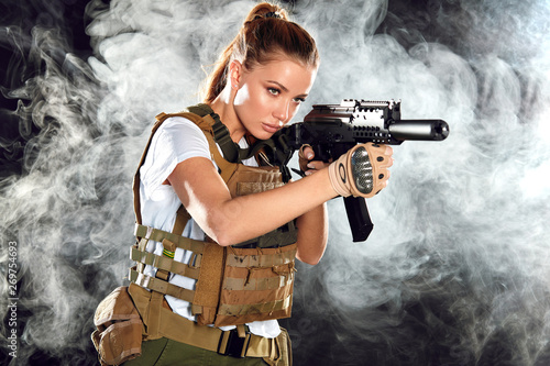 Calm concentrated woman marksman in sniper gear holding rifle in hand aiming at Canvas Print