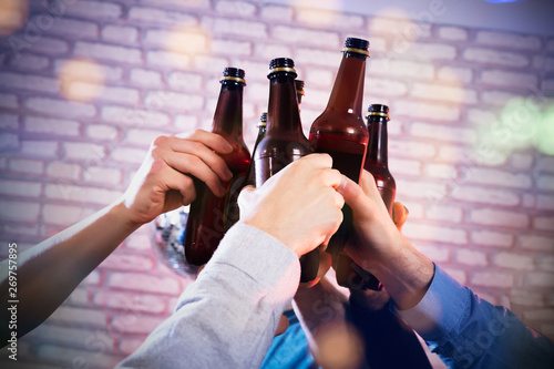 Hands Raising Toast With Beer Bottles At Bar