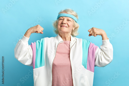 Happy, proud elderly attractive woman flexing both arms in the air with fists pressed showing strength or success, celebrating sport achievements. - 269758259