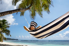Young Woman Relaxing On Hammock Over The Beach