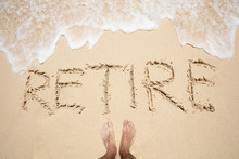 Man's Foot Near The Word Retire On Sand