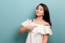 This Is Me. Portrait Of Proud Beautiful Brunette Young Girl With Black Straight Hair In White Dress Standing, Pointing Herself And Looking At Camera. Indoor Studio Shot Isolated On Blue Background.