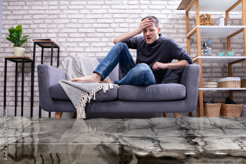 Upset Man In The Room Flooded With Water Wallpaper Mural