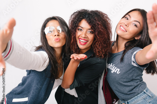 Valokuva  Close-up photo of smiling asian girl with tanned skin making selfie with her international friends