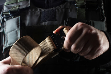 Soldier in tactical vest holding belt view closeup.