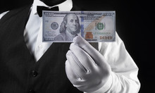 Waiter Holding Dollar Banknote In White Glove.