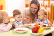 Leinwandbild Motiv Kids have a lunch in day care centre. Children eating healthy food in kindergarten. Nursery teacher with babies at table