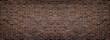 Wide red shabby brick wall texture. Old masonry panorama. Dark rough brickwork panoramic background