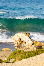 Large Golden Boulder With Iceplant In Front Of Cresting Torqouise Wave With Backspray Foam