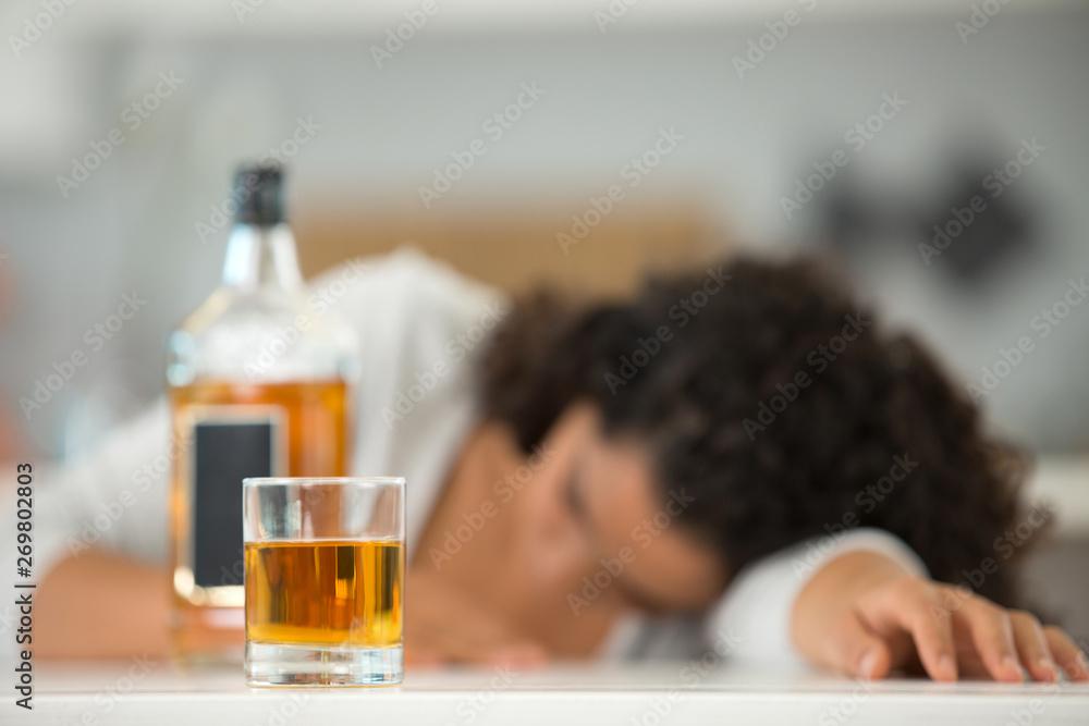 Fototapeta woman slumped over beside a bottle of alcohol