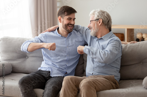 Obraz Happy grown son and senior dad relax at home together - fototapety do salonu