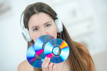 Portrait Of Lady Wearing Headphones Holding Three Cds