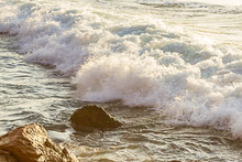 Pastel Colored Foam Rolling Infront Of Wave Towards Rocky Shore With Rocks