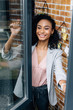 smiling african american Casual businesswoman opening window in loft office